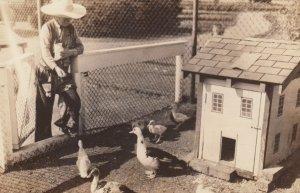 RP: DETROIT , Michigan , 1930s ; Cowboy feeding ducks at zoo