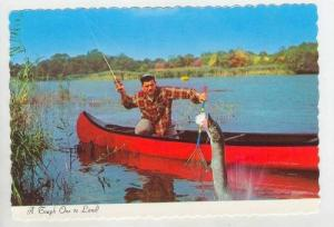 Man catches Northern Pike fish out of canoe, USA 40-60s