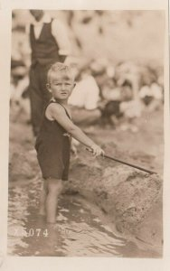 RP: Young boy playing in water with a stick , 1920-40s