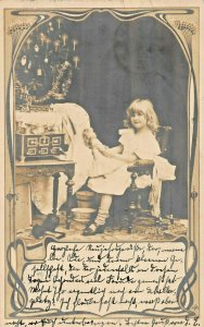 YOUNG BLONDE GIRL HOLDING DOLL-CHRISTMAS TREE~1903 GERMAN REAL PHOTO POSTCARD