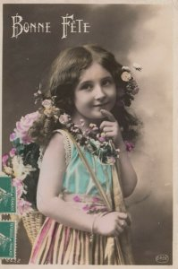 RP: BONNE FETE, PU-1915; Smiling girl carrying basket of roses on back