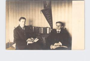 RPPC REAL PHOTO POSTCARD TWO YOUNG MEN READING WALDORF COLLEGE PENNANT ON WALL