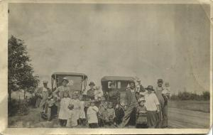 Two Proud Families in Front of their Old Cars of Unknown Brand (1920s) RPPC