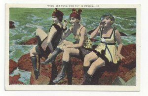 FLORIDA, 1920-30s; Come and Swim with Us Girls sitting on rocks at the beach
