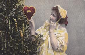 CHRISTMAS; Young lady holding red heart next to decorated tree, bonnet, 00-10s