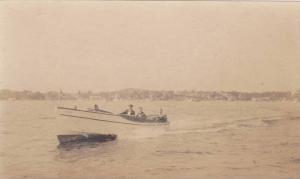 RP; Two Men on Motor boat, shoreline in background, 00-10s