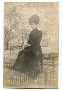 100812 RPPC Real Photo Postcard Woman Sitting on Fence - Big Hat Swisher IA