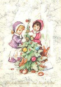 Sisters decorating Christmas tree Postcard