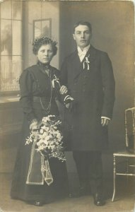 Early studio photo postcard portrait of a couple possibly groom and bride