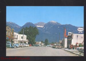RONAN MONTANA DOWNTOWN STREET SCENE 1960's CARS STORES VINTAGE POSTCARD