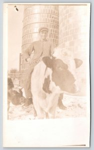 Real Photo Postcard~Farm Boy Rides Cow~Calf Sticks Nose in Pic~Silo~c1912 RPPC