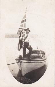 RP: Man holding flag while in boat , Canada , 00-10s