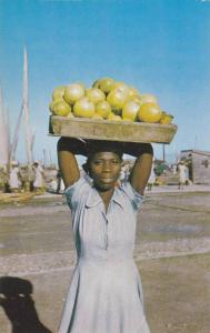 Tantine, Girl holding basketful of grapefruits to sell, Port-au-Prince, Haiti...