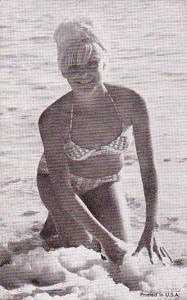 Pin-up blond girl in bikini kneeling at the ocean shore, 30-50s