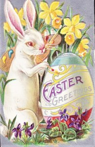 Easter Bunny painting a big Easter Egg says EASTER GREETINGS EMBOSSED. UNUSED