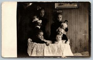RPPC You Kids Are Too Big For The Bassinet!~Older Sisters Hold Dollies~c1909 PC