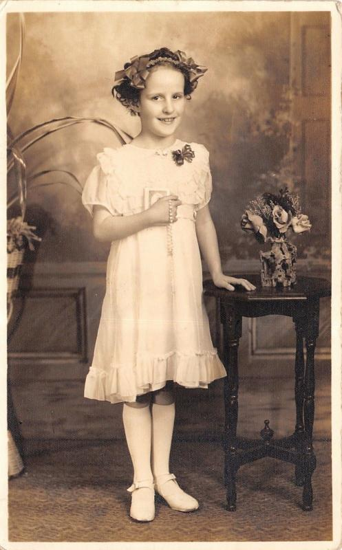 RPPC Little Girl Holds Rosary~Little Bible? Flowers in Her Hair & On Stand 1920s