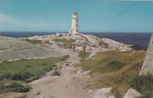 Tourists walk down the rocky path to the Lighthouse,  Peggy's Cove,  Nova Sco...