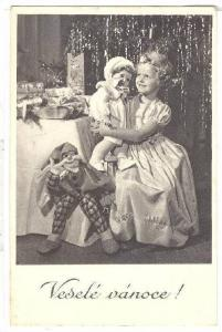 RP; Smiling girl holdingdoll sitting by table piled with gifts, Vesele Vanoce...