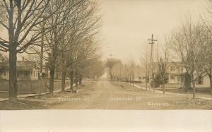 Hopkinton IA Dirt Uphill Street w/Many Nice Homes w/Porches RPPC c1907 Gearhart
