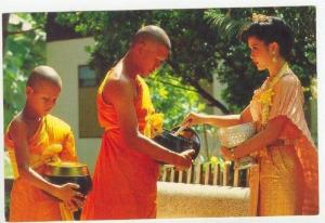 Thailand, 60-70s   Girl making merit by giving foods to Thai priest