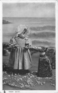 TUCK RPPC~Our Darling Series~Lass w/Sunbonnet Shovels Rocks into Sand Pail 1910