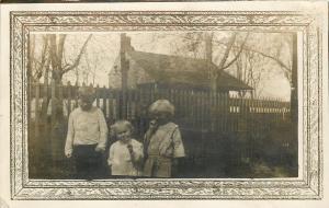 Real Photo Postcard~Rustic Border,Home~Picket Fence~3 Little Kids, 1 Bites Thumb