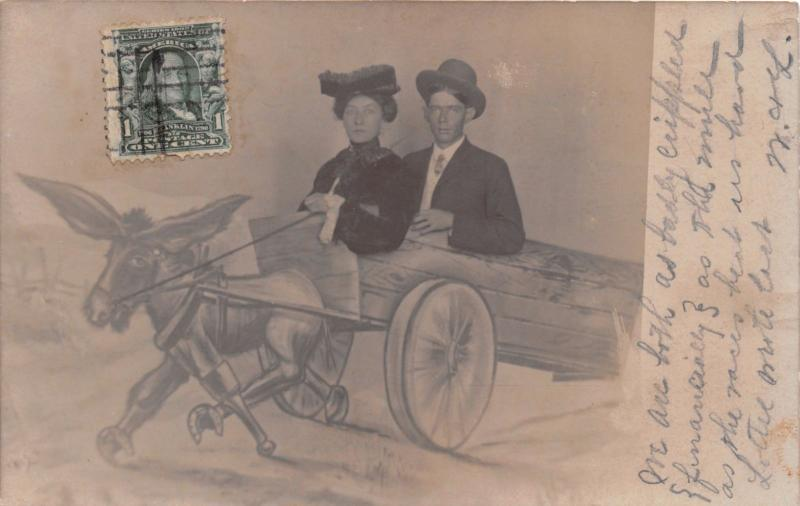 MAN & WOMAN POSE~DONKEY PULLING WAGON BACKDROP REAL PHOTO POSTCARD 1900s