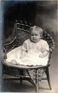 rppc Toddler girl in white dress sitting in wicker chair