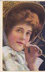 Woman wearing bonnet chewing on 'A Hayseed', PU-1908