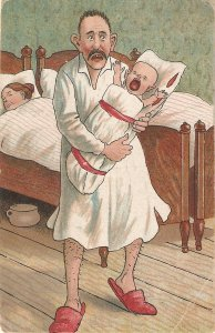 Father with crying baby. Mother in bed. Humorous vintage postcard