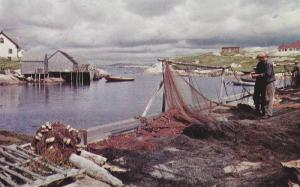 Fishermen mend their nets beside the peaceful inlet,  Peggy's Cove,  Nova Sco...