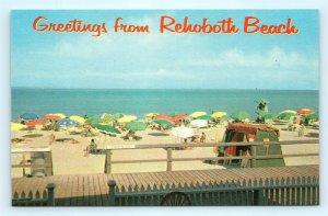 Postcard DE Rehoboth Beach Greetings View of Beach Boardwalk Umbrellas J16