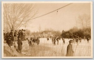 RPPC Small Bundled-Up Crowd on Hill Watches Ice Skaters Below~Man Sneaks~c1920