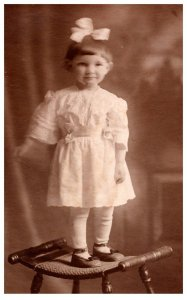 Young Girl standing on Chair ,Bow in hair