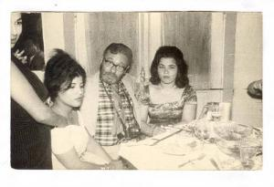 RP; Two Arab girls & white man at dinner, Port Said, Egypt, 1940-50s