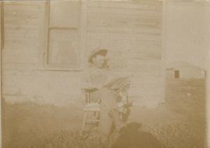 RP: PLEASANT LAKE , North Dakota , 1910 ; Man Reading Newspaper at Cabin