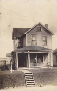 RP; General View of two-story house with woman sitting on porch rail, PU-1910