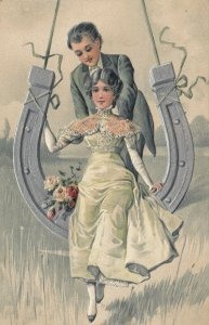 PFB 5486, PU-1909; Groom pushing his wife on a silver horse shoe, Roses