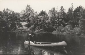 RP: NEW LONDON , New Hampshire, 1930s ; Man fishing in a canoe