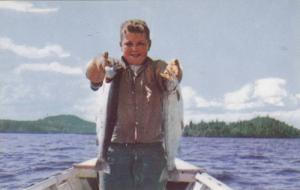 Boy holding up two rainbow trout from Stuart Lake, British Columbia, Canada, ...