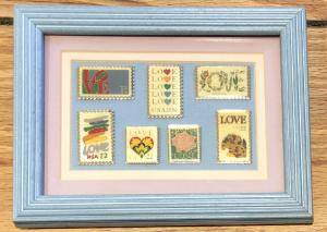 7 Love Stamp Pins Under Glass in a Wood Frame