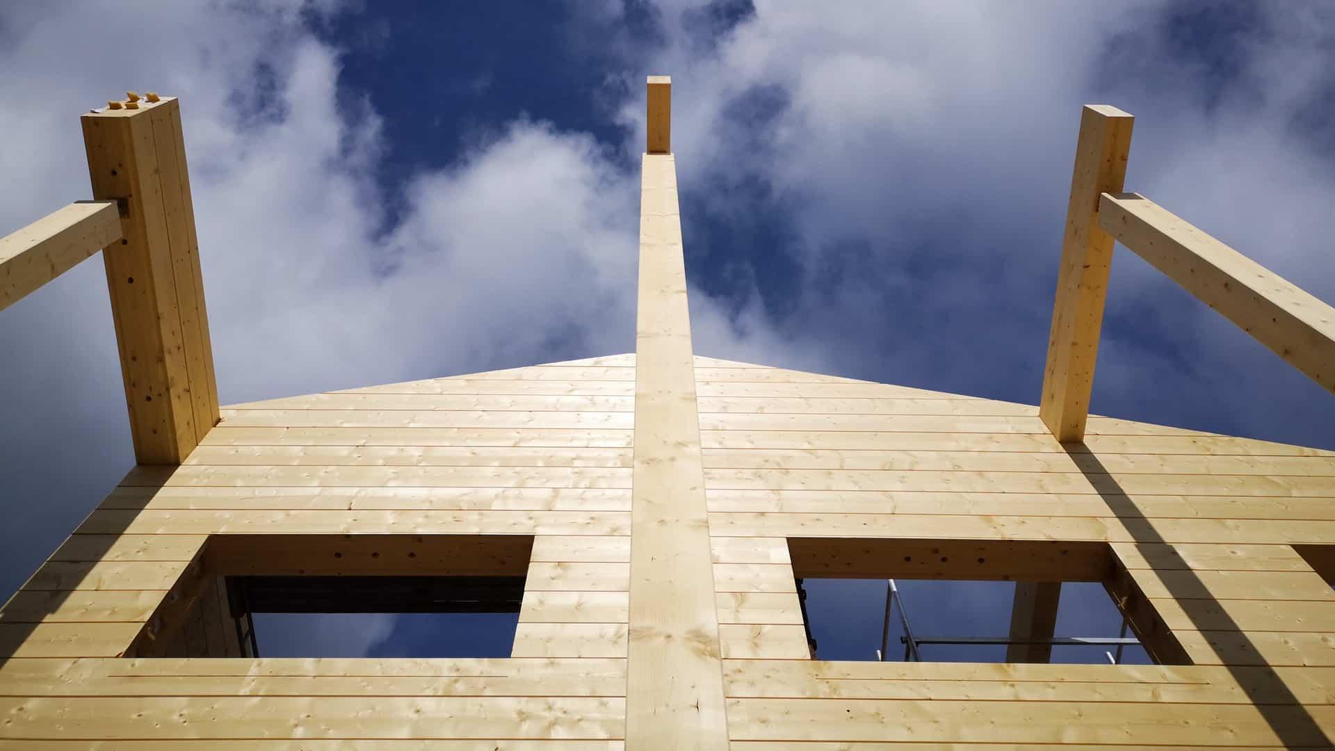 Työmaakuva hirsitalon rakennusprojektista. Hirsikehikko kohoaa sinistä taivasta kohden.