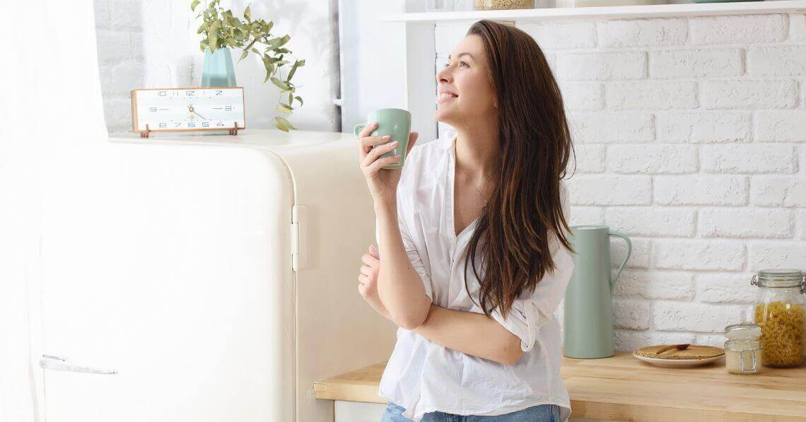 Happy young woman smiling in the kitchen