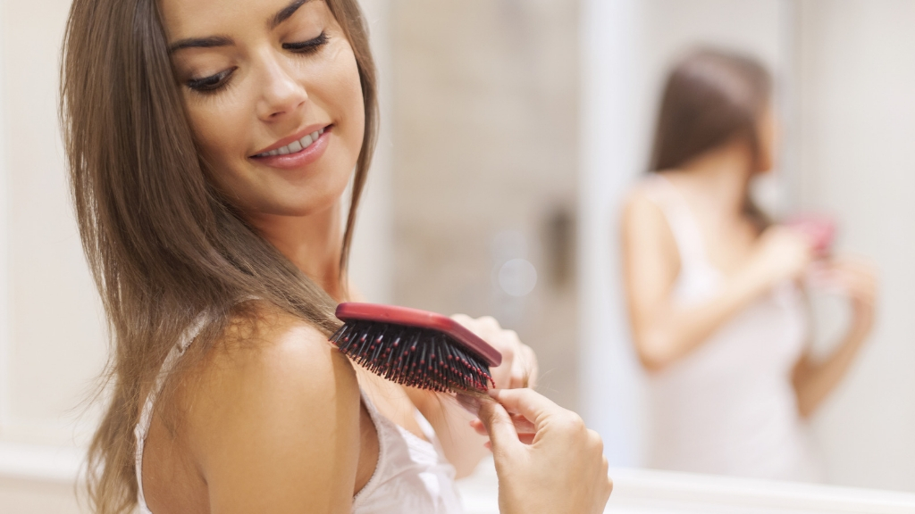 A woman brushes her hair