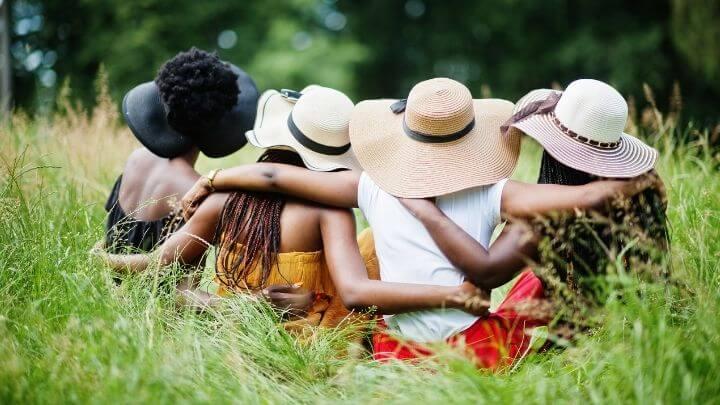 Women in a meadow wearing hats