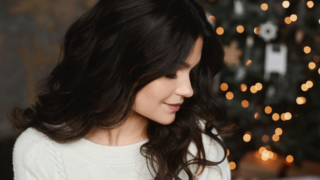 A woman with wavy dark hair near Christmas lights