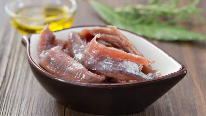 Anchovies in a dish with oil and herbs
