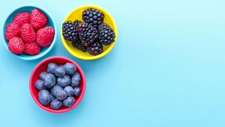 Blueberries, raspberries and blackberries in 3 small yellow bowls