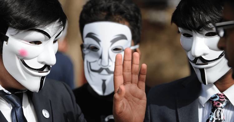 Three men wearing Guy Fawkes masks talking to each other